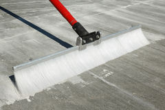 Concrete finishing broom. Close view of a concrete finishing broom with plastic bristles and red handle on a textured brushed finish royalty free stock photography