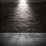 Concrete floor and brick wall with spot light illumination Royalty Free Stock Photography