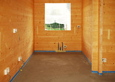 Concrete Floor in New Build. A newly paid concrete floor in a newly built wooden (fir) house. The blue foam material is protecting the wood from the concrete and royalty free stock images