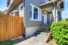 Concrete floor porch of siding house. Wooden fence and green bushes Stock Images