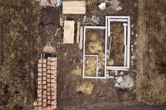 Concrete foundation for basement of future house, stacks of bricks and building timber logs for construction on sunny summer day,. Aerial view stock photo