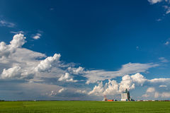 Concrete Grain Elevator Under Big Blue Sky. With Dramatic White Clouds Royalty Free Stock Photography