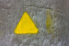 Concrete gray wall with yellow triangle Stock Image