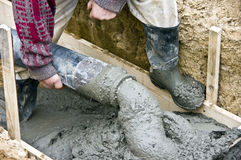 Concrete hose. A pipe (hose) pouring out with liquid concrete, part of house building process stock image