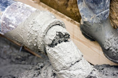Concrete hose. A pipe (hose) pouring out with liquid concrete, part of house building process stock images