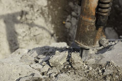 Concrete jack hammer. Jack hammer used for breaking, chipping, and demolishing concrete close-up of bit with crushed concrete and shadow Stock Photography