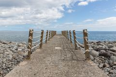 Concrete jetty and iron fence with ropes Stock Photo
