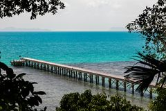Concrete jetty surrounded by the tropical forest with blue ocean Stock Photo