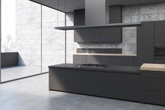 Concrete kitchen interior, black cabinets, side. Concrete kitchen interior with a concrete floor, black cabinets and consoles with built in cookers and a balcony Stock Image