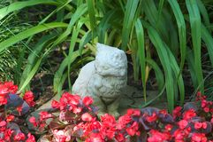 Concrete Kitty. Concrete cat sitting in a flower garden Royalty Free Stock Photography
