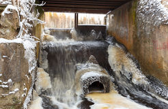 Concrete lake weir with non-freezing water stream in winter Royalty Free Stock Photography