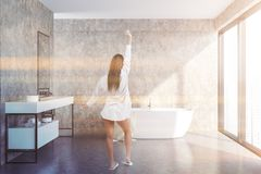 Concrete loft bathroom, tub and sink, girl stock photos