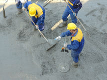 Concrete mix leveling. Construction workers spreading freshly poured concrete mix at the building site
