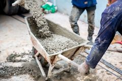 Concrete mixed cement pouring from mortar grinder truck to trolley holding by worker stock image
