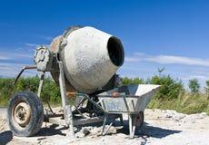 Concrete mixer. A typical concrete mixer and a wheelbarrow, sunny day royalty free stock photography