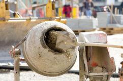 Concrete mixer on construction site. Close up of shovel throwing cement into concrete mixer on construction site Royalty Free Stock Photos