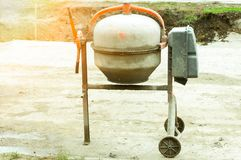 Concrete mixer is left after working time at construction site on the street with sunlight. royalty free stock images