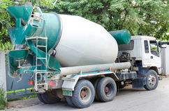 Concrete mixer truck with green cab over trees Royalty Free Stock Photo