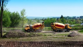 Concrete mixer trucks. Two concrete mixer lorries working at building site Stock Photos