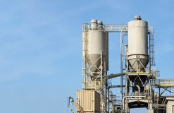 Concrete mixing silos. Blue sky background. Wispy clouds, room for text. Horizontal composition Royalty Free Stock Photos