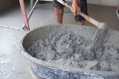 Concrete mixing step of sand cement and water by construction workers. Pouring water to grunge cement tray at outdoor site stock image