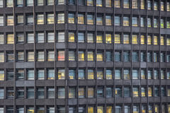 Concrete office building with illuminated windows. Full frame of a concrete building with illuminated windows at night Royalty Free Stock Photo