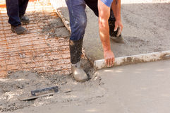 Concrete parking places. Workers work on concreting parking spaces in front of the house. Mason worker leveling concrete with trowels mason hands spreading Royalty Free Stock Images