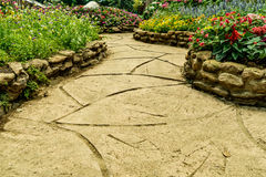 Concrete Pathway in garden. Concrete pathway with colorful flowers in the park Royalty Free Stock Photo