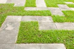 Concrete pavement on grass Royalty Free Stock Photos