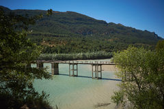 Concrete pedestrian bridge over a bay among green hills Royalty Free Stock Images