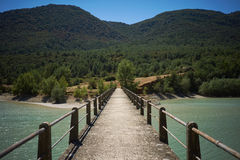 Concrete pedestrian bridge over a bay among green hills Royalty Free Stock Image