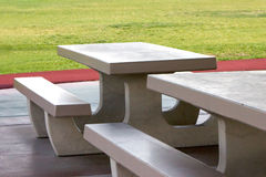 Concrete picnic tables. Two gray concrete picnic tables side by side in a park with green grass behind stock images