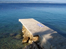 Concrete pier on the beach. Wild croatian beach with rocks and a concrete pier Stock Image