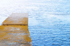 Concrete pier and blue lake, free space. Bridge and blue water, Stock Photos