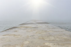 Concrete pier in a foggy day. Concrete pier goes away into the sea in a foggy day royalty free stock photography