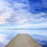 Concrete pier or jetty and on a blue lake and sky reflection on water. Stock Images