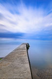 Concrete pier or jetty on a blue sea and cloudy sky. Normandy, France Stock Photo
