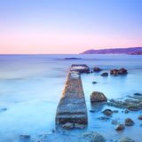 Concrete pier or jetty and rocks on a blue sea. Hills on backgro Royalty Free Stock Photos