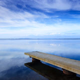 Concrete Pier Or Jetty And On A Blue Lake And Sky Reflection On Water. Royalty Free Stock Image