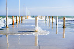 Concrete pier with rusty white bars on the sea side. Waves and horyzon Royalty Free Stock Photo