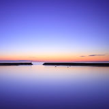 Concrete pier silhouette and blue ocean on twilight sunset Stock Photography