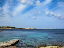 Concrete pier with a turquoise blue sea in the afternoon with blue cloudy sky stock photography