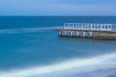 Concrete pier, with wooden buildings on it, washed by the waters of the Black Sea. The photo was taken on a long exposure. stock photography