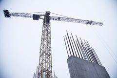 Concrete pijlers op industriële bouwwerf De bouw van wolkenkrabber met kraan, hulpmiddelen en versterkte staalbars royalty-vrije stock foto's