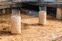 Concrete pillar with steel rods on dirt ground construction site Stock Photos