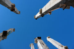 Concrete pillars at abandoned construction site. On blue sky background Stock Photo