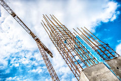 Concrete pillars on industrial construction site. Building of skyscraper with crane, tools and reinforced steel bars. Concrete pillars on industrial construction royalty free stock image