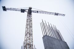 Concrete pillars on industrial construction site. Building of skyscraper with crane, tools and reinforced steel bars royalty free stock photos
