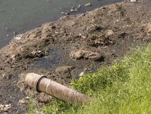 Concrete pipe discharges sewage into Pinheiros River. In Sao Paulo city stock photo