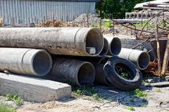 Concrete pipes and old tire on the construction site. Concrete pipes in a pile and an old tire on a construction site royalty free stock photography